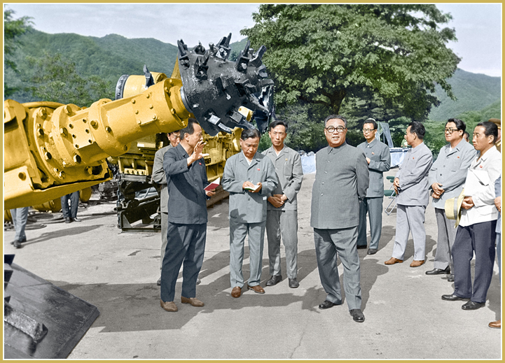 Kim Il Sung examines a coal cutter produced at the May 10 Factory (July 1980).