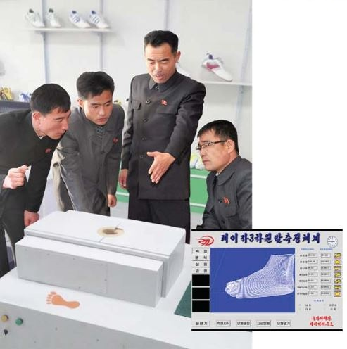 Kim Kum Chol (second right) explains the technical speci fi cation of the laser 3D foot measuring device.